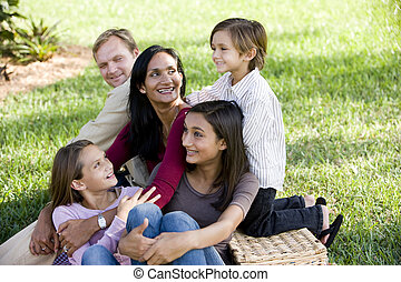 Happy interracial family of five enjoying a picnic in the park