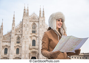 Smiling woman traveler with map looking aside near Duomo,...