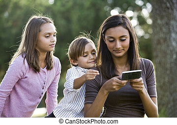 Teenage girl with mobile phone texting, younger siblings watch