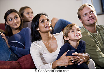 Family of five sitting together on sofa watching TV