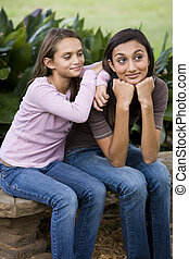 Affectionate sisters sitting together on bench