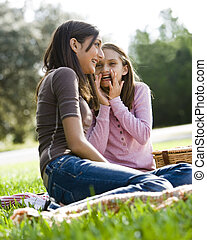 Girls whispering to each other at picnic in park