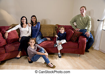 Portrait of interracial family of five sitting on couch