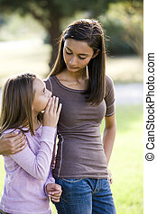 Girl whispering to her older teenage sister - Ten year old...