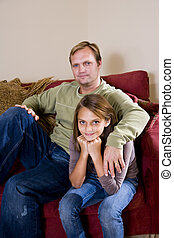 Father with ten year old daughter on couch at home