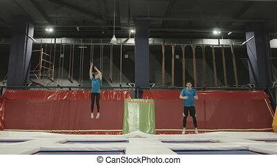 Three Professional gymnasts doing trcks on trampoline...