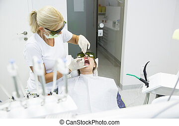 Dentist using a modern diode dental laser for periodontal...
