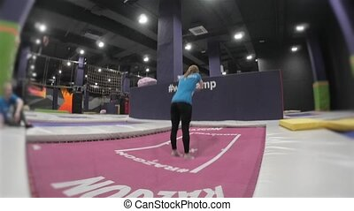 Professional Girl Gymnast doing trcks on trampoline. Flips in air. High Extreme Jumps by Professional Athlete.