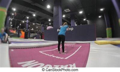 Professional Girl Gymnast doing trcks on trampoline. Flips...