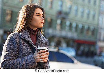 Beautiful smiling woman  holding a cup of coffee in her hands in the city