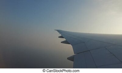 wing of airplane flying in blue sky - travel,...