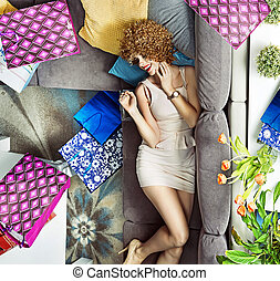 Young lady with many shopping bags lying on the sofa - Young...