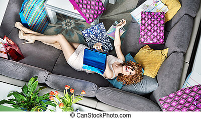 Satisfied young lady lying among many shopping bags -...