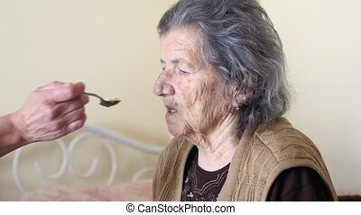 """""""old woman get support for eating, feed by daughter"""" -..."""