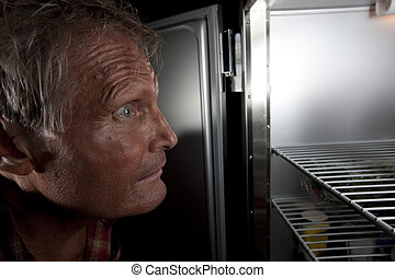 Intense Man Staring Into Refrigerator - Close-up profile of...
