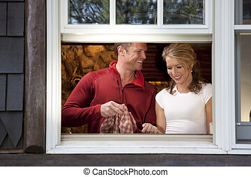 Smiling Couple Doing Dishes at Kitchen Window - View from...