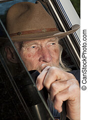 Senior Man With Cowboy Hat Sitting in Vehicle - Cropped...