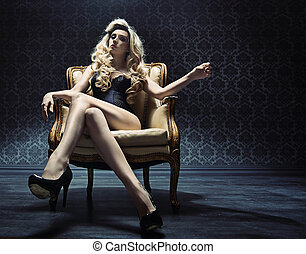 Alluring blond lady sitting on a vintage armchair - Alluring...