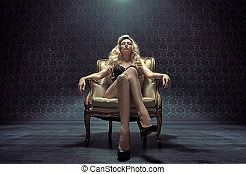 Dominating blond woman sitting on the armchair - Dominating...