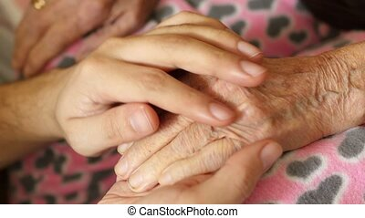 grandson man holding hand of very old senior woman...