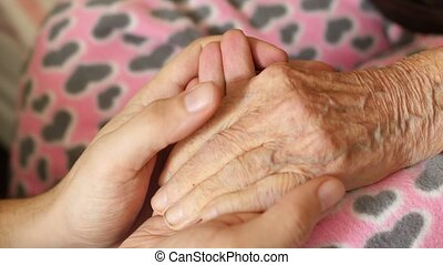 grandson man holding hand of very old senior woman grandmother