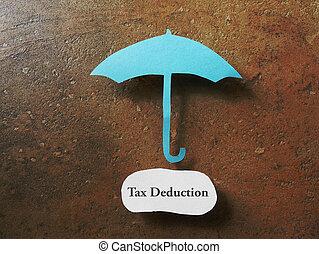 Tax deduction concept - Paper umbrella over a Tax Deduction...