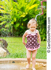 Cute little child girl in swimsuit bathing in the shower on...