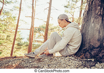 Sportsman tying shoelaces outdoor near the tree at sunny day