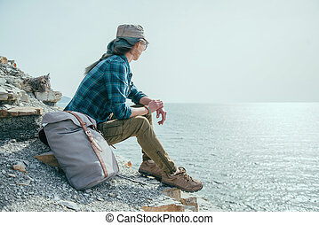Traveler woman looking at sea - Traveler young woman sitting...