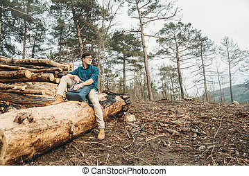 Man sitting on felled wood trunks - Hiker young man with...