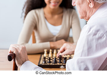 Carer, patient and duel in chess - Close-up of older man's...