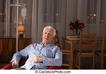 Man during home treatment - Image of ill senior man during...