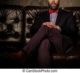 Old-fashioned bearded man sitting in comfortable leather sofa isolated on gray.