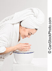 Young woman washing face with clean water - The young woman...