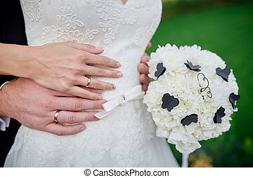 hands bride and groom with wedding rings a bouquet of white flowers