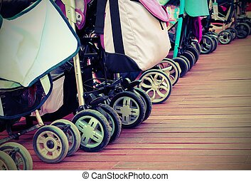 strollers for toddlers parked on the parquet floor of wood -...
