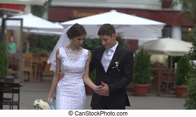 Bride and groom walking down the street, holding hands