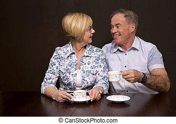 couple having a coffee - retired couple sitting by the table...
