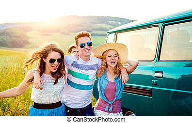 Young friends with campervan, green nature and blue sky -...