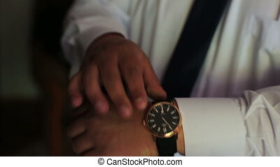Man putting on wrist watch. Isoalted on black background,...