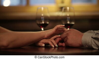 Close up of loving couple holding hands during romantic dinner. Glasses of red wine on background