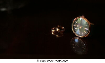 Golden wedding rings and hand clock isolated on black background