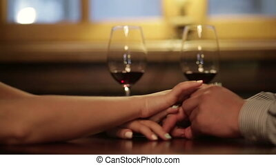 Close up of loving couple holding hands and clinking glasses of red wine during romantic dinner.