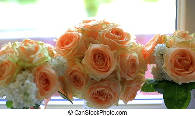Bouquet of beige roses in vases on the windowsill. Wedding...