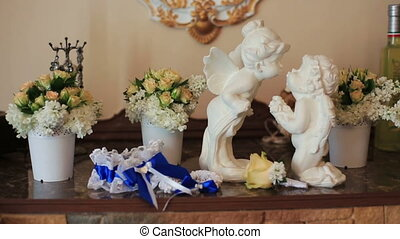 White ceramic sitting angels kissing on flowers background
