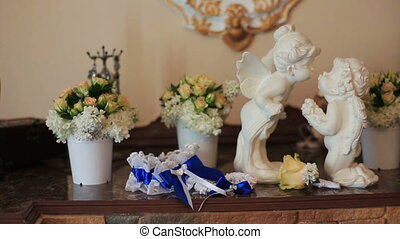 White ceramic sitting angels kissing on flowers background.