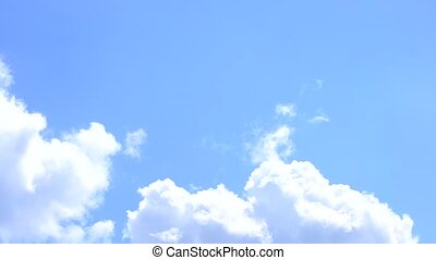 White cirrus and cumulus clouds move on background of blue sky