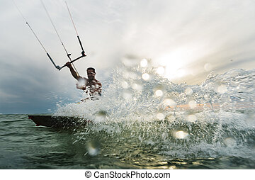Man surfing and splashing to the camera - a young man...