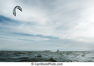 Kitesurf in Sanctipetri - A man doing kitesurfing in front...