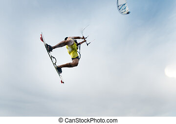 Surfer flying with his kite - a surfer flying through the...